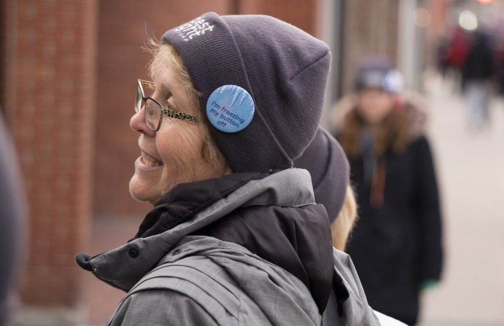 "Woman wearing grey Coldest Night toque and ""I'm freezing my button off"" button"