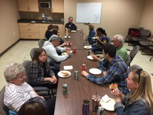 Ray of Hope volunteers sitting at a table eating pizza