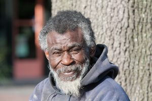 An older black man smiles at the camera
