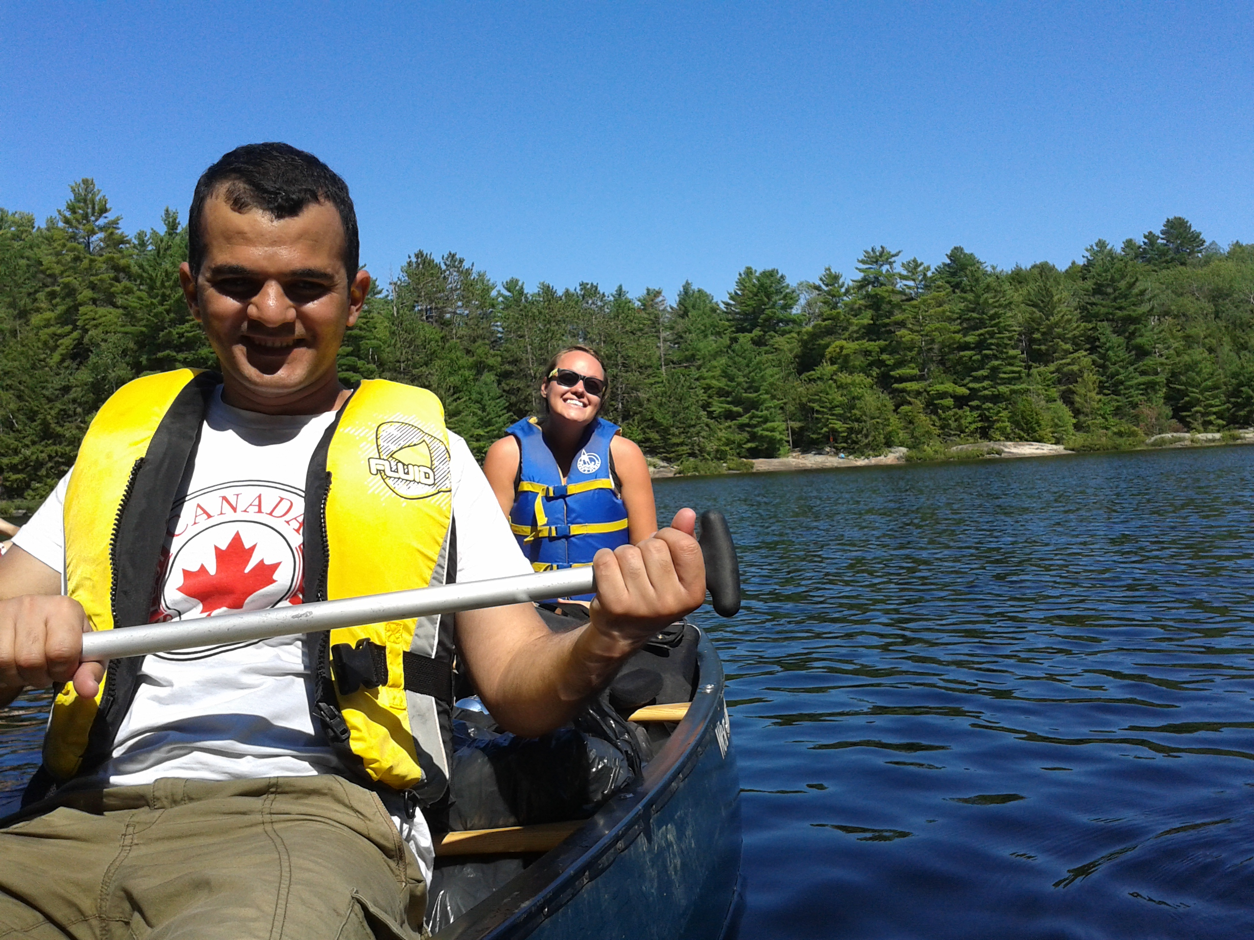 Smiling man and woman paddle a canoe