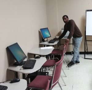 Ray of Hope's program co-ordinator Boris Emanuel adjusts a computer in the WRAP Room.