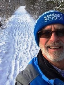 Jon Hill wearing a CNOY tuque while walking on a trail