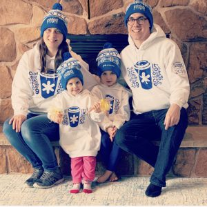 Brian Keith Ellis, his wife and two small daughters sit in front of a fireplace while wearing CNOY toques.