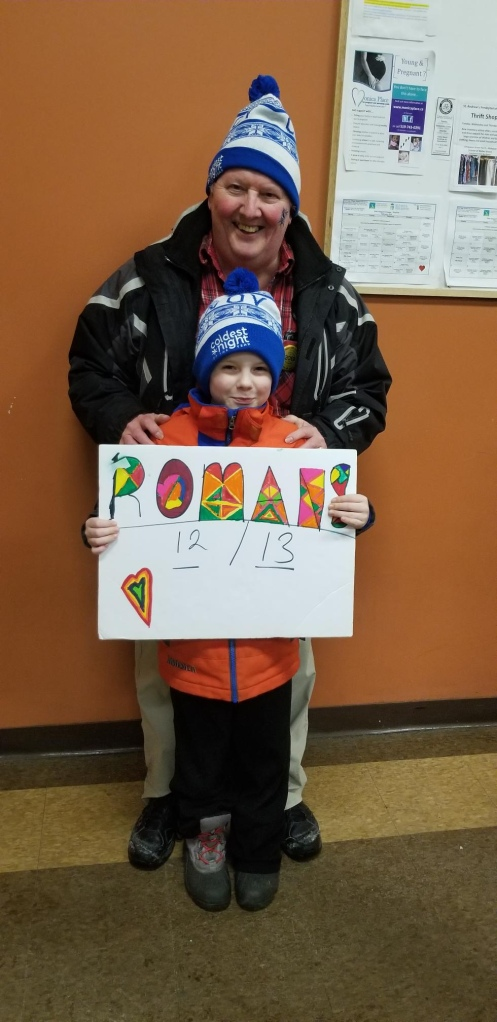 A young boy and an older man wearing winter coats and hats hold a sign that reads 12 or 13 Romans