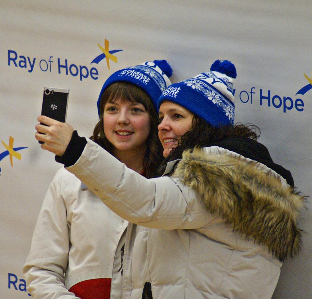 Mother and daughter wearing white and blue CNOY toques take a selfie