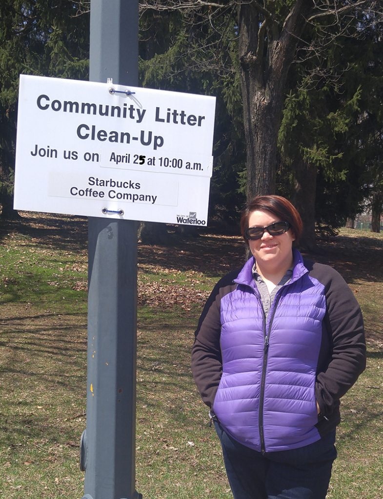 Woman wearing sunglasses stands nest to a community cleanup sign attached to a lamppost