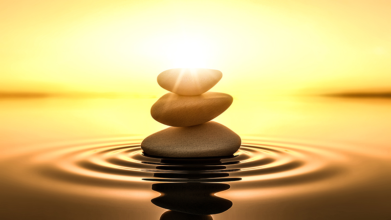 stones rising out of rippled water against a rising sun
