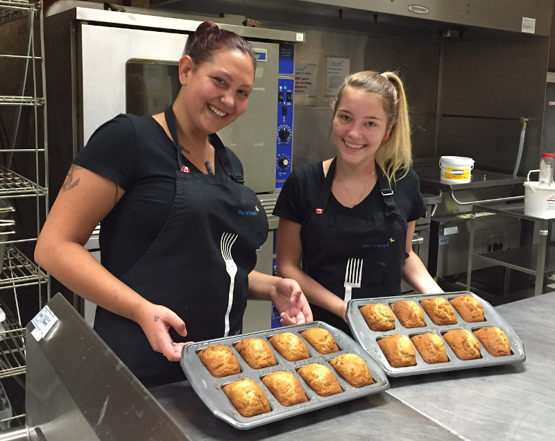Two young women display trays of mini-loaves